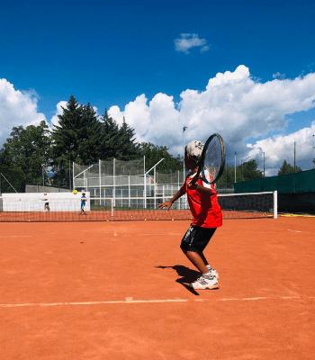 Enfants jouant au tennis sur un court avec de la terre battue au soleil