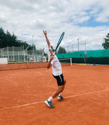 Joueur de compétition en plein engagement, la balle de tennis déjà en l'air