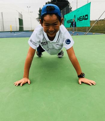 Petit enfant faisant la planche et souriant sur un court de tennis en extérieur, avec le t-shirt BTA