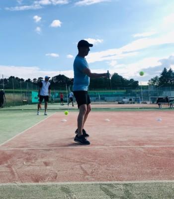 Homme tapant dans une balle sur un court de tennis en extérieur