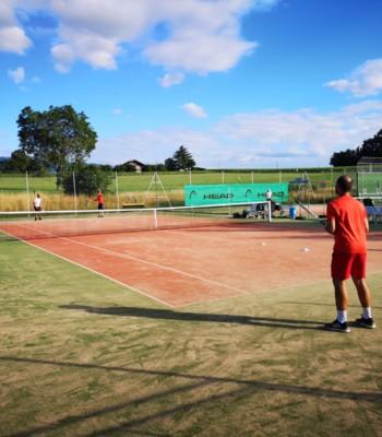 Joueurs de tennis en plein match sur un court de tennis extérieur, en plein soleil